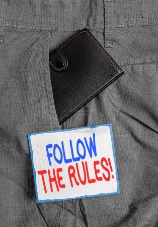 Photo pour Texte d'écriture suivez les règles. Photo conceptuelle aller avec des règlements régissant la conduite ou la procédure Petit petit portefeuille à l'intérieur de la poche avant de pantalon d'homme près du papier de notation - image libre de droit