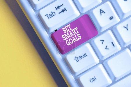 Photo pour Rédaction de main conceptuelle montrant set Smart Goals. Concept signifiant donner des critères pour guider dans l'établissement des objectifs Clavier pc blanc avec papier de note au-dessus du fond blanc - image libre de droit