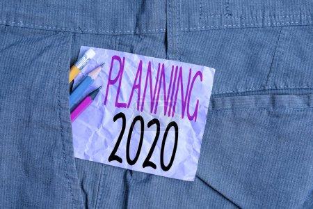 Photo pour Ecriture conceptuelle montrant Planning 2020. Signification du concept Commencez par la fin de l'esprit Positionnement Objectifs à long terme Matériel d'écriture et papier à notes violettes dans la poche intérieure du pantalon - image libre de droit