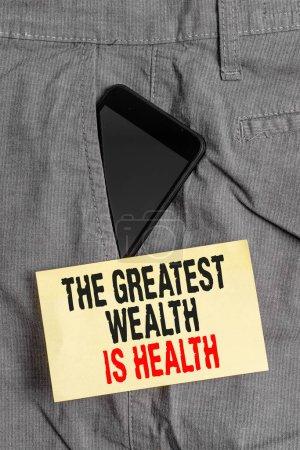 Photo pour Texte d'écriture de mots La plus grande richesse est la santé. Photo d'affaires présentant beaucoup sacrifient leur argent juste pour être dispositif sain de Smartphone à l'intérieur de la poche avant formelle de pantalon de travail près du papier de note - image libre de droit