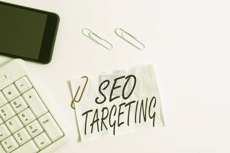 Text sign showing Seo Targeting. Conceptual photo Specific Keywords for Location Landing Page Top Domain White pc keyboard with empty note paper above white background and mobile phone.