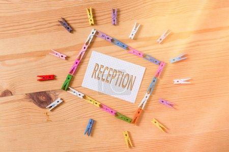 Photo pour Note d'écriture montrant la réception. Concept d'entreprise pour le rassemblement social souvent dans le but d'étendre un accueil Papiers à pinces à linge colorés rappel vide plancher en bois bureau de fond - image libre de droit