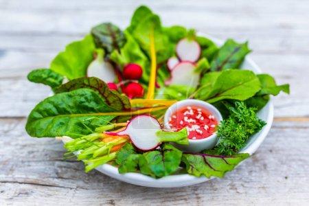 Foto de Crea ensalada de verduras de temporada sobre un fondo de madera. Alimentación vegetariana. - Imagen libre de derechos