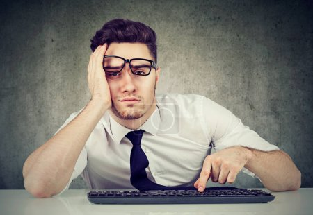 Photo for Sleepy bored man employee sitting at desk has no motivation to work - Royalty Free Image