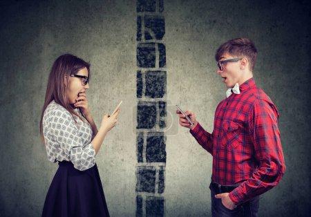 Sorprendido joven pareja hombre y mujer separados por la pared de mensajes de texto entre sí en el teléfono móvil