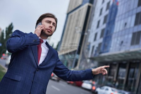 Confident businessman caching taxi