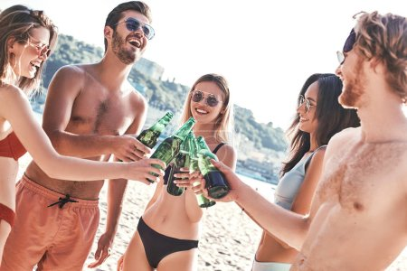 Photo for Enjoying carefree time with friends. Cheerful young people spending nice time together while sitting on the beach and drinking beer - Royalty Free Image