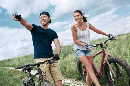 Photo for Happy couple racing on a bike along the sand and grass high in the mountains. - Royalty Free Image