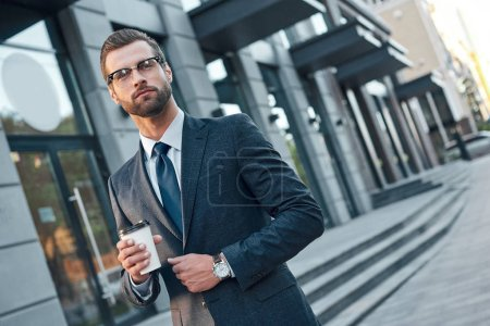 Quick coffee break. Good looking young man in full suit and glasses looking away and holding disposable cup while standing outdoors