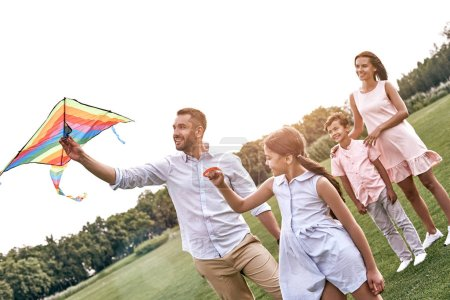 Photo for Weekend activities. Family with a kite walking on field in nature smiling cheerful - Royalty Free Image
