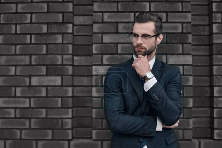 Photo for A young businessman thought about the future prospects. A young businessman with his hand propped his chin, his gaze is directed to the side - Royalty Free Image