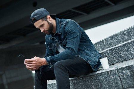 Photo pour Loisirs en plein air. Jeune homme élégant assis sur les escaliers dans la rue de la ville avec une tasse de café chaud en utilisant l'application sur smartphone joyeux - image libre de droit