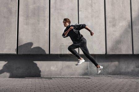 Photo pour L'athlète coureur court près du stade. Homme jogging entraînement concept de bien-être . - image libre de droit