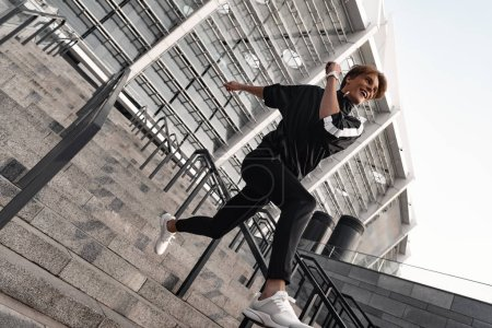 Photo for Athletic young man running downstairs. He wears sportswear and white sneakers. - Royalty Free Image