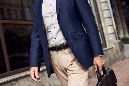 Photo pour Réfléchissez à une réunion d'affaires. Homme élégant en costume décontracté souriant tout en marchant à l'extérieur - image libre de droit