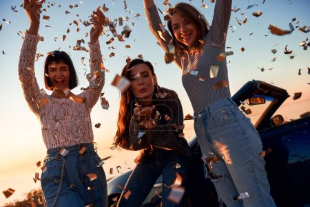 Cheerful young three women are dancing near the ca...