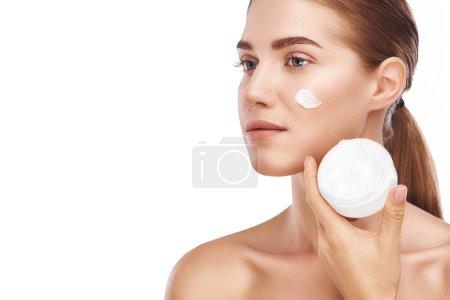 Photo pour Belles femmes joue droite avec facecream fermer photo studio sur fond blanc. Cheveux clairs, yeux gris - image libre de droit
