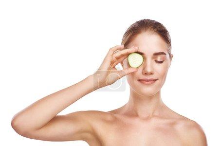Photo pour Magnifique visage de femme avec du concombre en gros plan photo studio sur fond blanc. Cheveux clairs, yeux gris, yeux fermés - image libre de droit