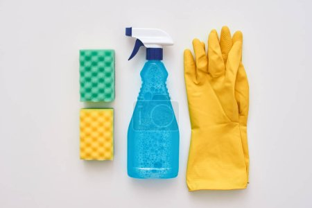 Photo for Good housekeeping. Spray bottle, yellow gloves and two cleaning sponges isolated - Royalty Free Image