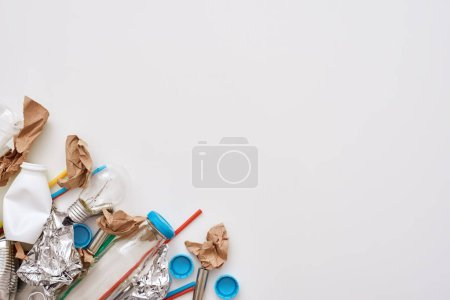 Photo for Protect the environment. Crumple foil, paper and plastic are lying on the floor isolated. Photo of different types of garbage unsorted at the left corner - Royalty Free Image