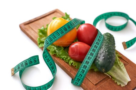 Photo for Stay fit. Healthy eating, dieting, slimming and weigh loss concept - close up of vegetables, measuring tape and salad - Royalty Free Image