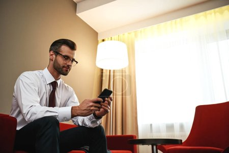 Photo for Business chat. Spectacled business man with suitcase and tablet sitting on sofa at hotel hall - Royalty Free Image