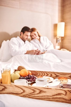 Breakfast in hotel room. Couple are hugging in hot...