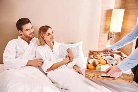 Breakfast in a bed. Couple are hugging in hotel ro...