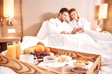 Food in a bed. Couple are hugging in hotel room be...