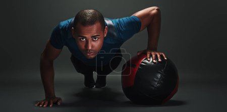 Photo for Front view portrait of concentrated, confident, sporty, athletic, attractive man making, showing push up position, isolated over dark background - Royalty Free Image