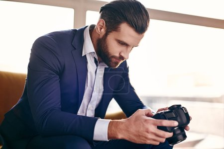 Photo for Close-up portrait of handsome young businessman in fashion suit who is looking at pictures on camera while sitting on sofa at office - Royalty Free Image