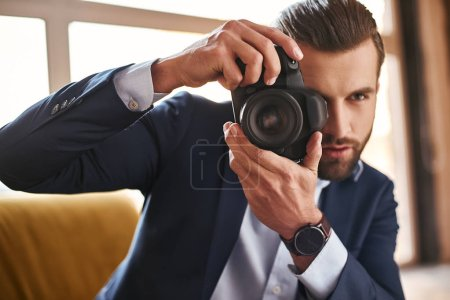 Photo for Young stylish businessman with camera in his hands taking pictures while sitting on sofa at modern office. Fasion look. Business style - Royalty Free Image