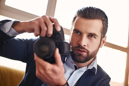 Photo for Handsome young businessman in stylish suit is holding camera and going to make a photo. Business look. Close-up - Royalty Free Image