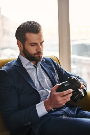 Photo for Photography is a Great Hobby...Close-up portrait of young bearded and well dressed businessman who is looking at pictures on camera. Fashion look. Bussiness style - Royalty Free Image