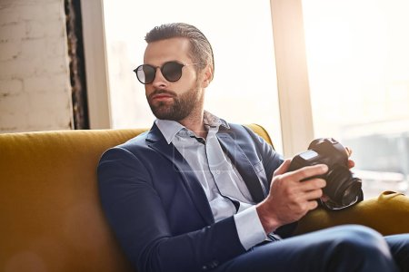 Photo for In search of inspiration. Successful young stylish businessman in sunglasses, is holding photo camera and thinking about something. Business style. Fashion look - Royalty Free Image