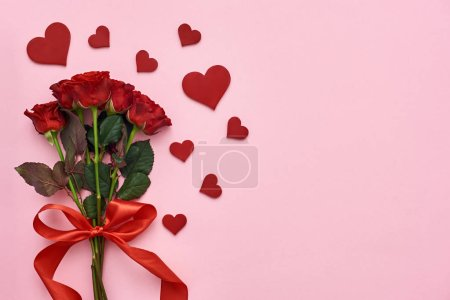 Photo pour Le véritable amour. Bouquet de roses avec ruban rouge pour elle avec des coeurs de papier décoratif sur fond rose - image libre de droit