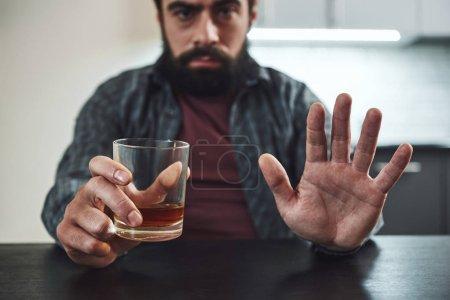 Photo pour Un barbu déprimé s'assoit à la table avec un verre de whisky à la main. L'homme refuse de boire de l'alcool. Concept d'alcoolisme masculin . - image libre de droit