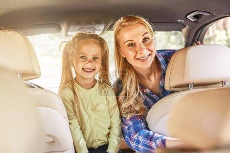 Photo pour Jeune mère caucasienne blonde avec une petite fille regardant la caméra et souriant à l'intérieur de la voiture. L'été, concept d'aventures - image libre de droit