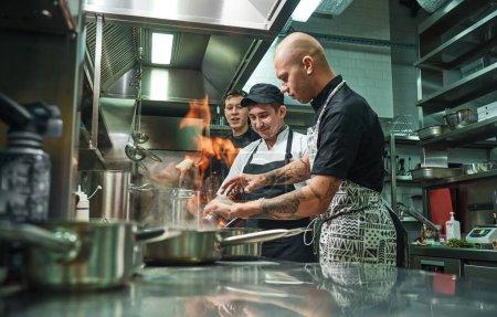 Photo pour Cuisine extrême. Chef professionnel enseignant à ses deux jeunes stagiaires comment flamber la nourriture en toute sécurité. Cuisine du restaurant. Processus de cuisson - image libre de droit