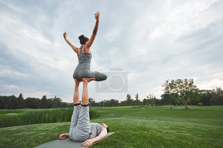 Photo for Beautiful poses with a partner. Strong man lying on a mat and balancing woman in lotus pose on his feet. Young couple doing acro yoga in nature. Healthy lifestyle concept. Acro yoga concept - Royalty Free Image