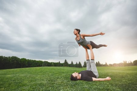 Photo for Healthy lifestyle. Strong man lying on grass and balancing woman on his feet. Young couple practising acro yoga in nature. Healthy lifestyle concept. Acro yoga concept - Royalty Free Image