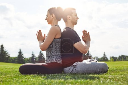 Photo for Balance your life. Young couple meditating together while sitting sitting in lotus pose back to back on a green lawn in open field. Meditation concept. Yoga concept. Healthy lifestyle - Royalty Free Image