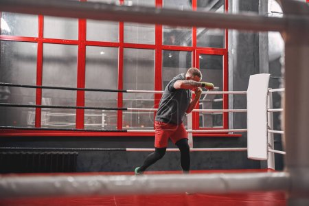 Photo for Handsome muscular sportsman in sports clothing training on boxing ring. Strong man doing shadow-boxing on red boxing ring in the gym - Royalty Free Image