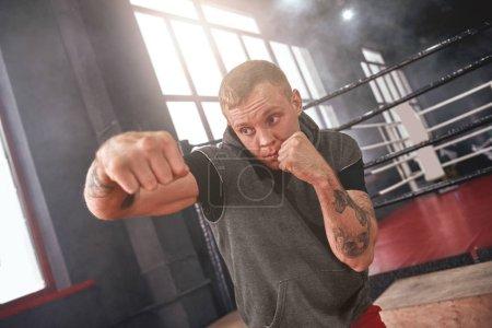 Photo pour Gros plan de confiant bel athlète en scène coup de poing de côté de vêtements de sport. Jeune homme boxe avec l'ombre tandis que debout en face de couleur ring de boxe - image libre de droit