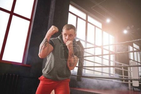 Photo pour Confiant bel athlète en jetant uppercut de vêtements de sport. Jeune homme boxe avec l'ombre tandis que debout en face de couleur ring de boxe - image libre de droit