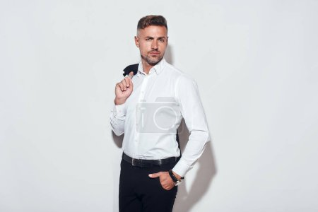 Photo for Totally handsome. Stylish businessman in classic wear holding his jacket and keeping hand in pocket while standing against grey background. Men beauty. Business look - Royalty Free Image