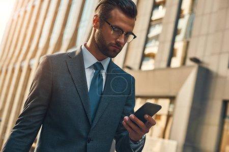 Photo pour Message important. Portrait d'un bel homme d'affaires barbu en tenue officielle utilisant un téléphone intelligent lors de ses promenades à l'extérieur. Concept d'entreprise. Concept numérique - image libre de droit