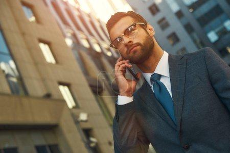 Photo pour Une journée chargée. Portrait d'un bel homme barbu en costume parlant par téléphone avec un client tout en marchant à l'extérieur. Concept d'entreprise - image libre de droit