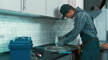 Photo pour Portrait d'un plombier sérieux portant uniforme installant des tuyaux d'égout dans une cuisine. Plan horizontal - image libre de droit