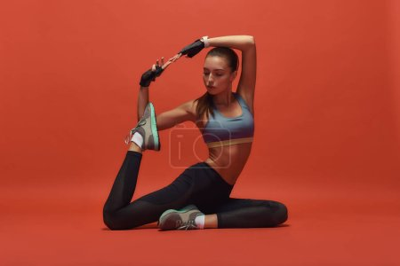 Photo for Full-length portrait of young girl in sportswear sitting while stretching isolated over red background. Fitness and work out concept. Horizontal shot - Royalty Free Image